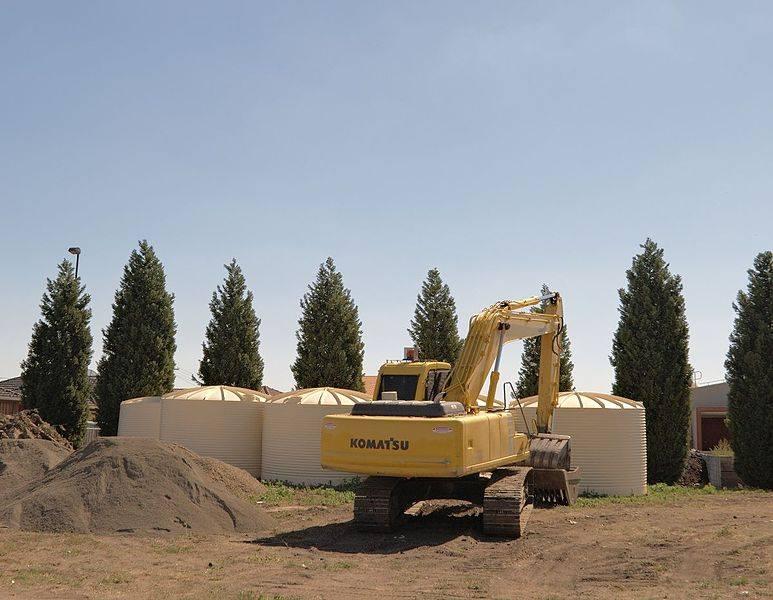 Tractopelle sur un chantier d'enfouissement d'un système de récupération d'eau de pluie