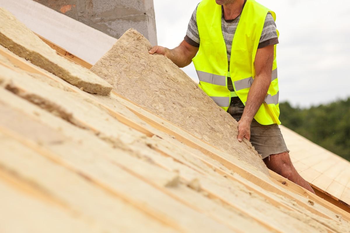 Ouvrier installant un matériau d'isolation toiture